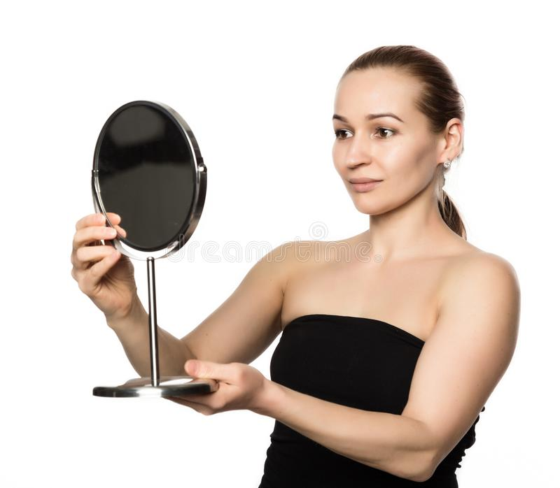 Young woman performs anti-aging exercises. face fitness. girl looks in the mirror stock photography