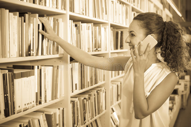 Young woman with phone in book shop. Portrait of smiling young woman picking textbooks for school while talking on telephone in shop stock photography