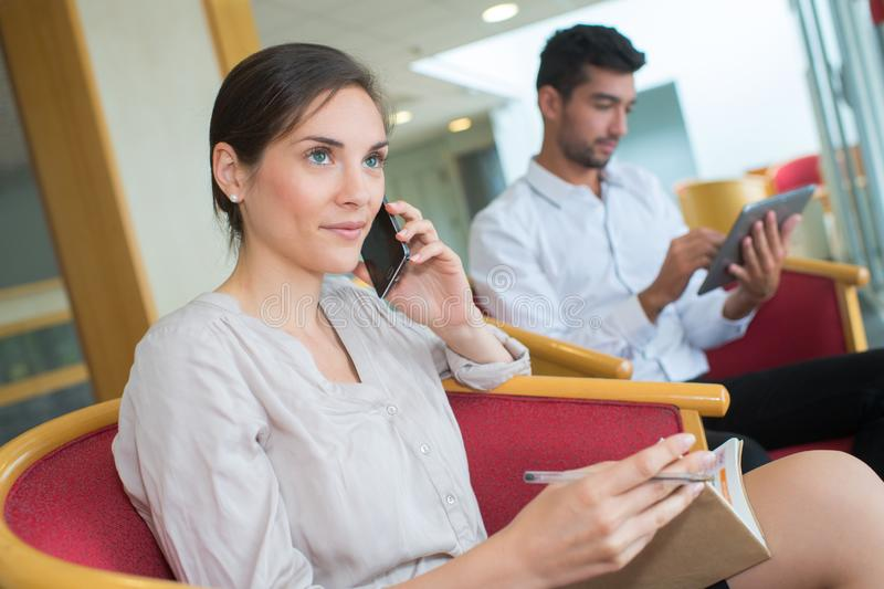 Young woman on phone while waiting in aeroport stock photography