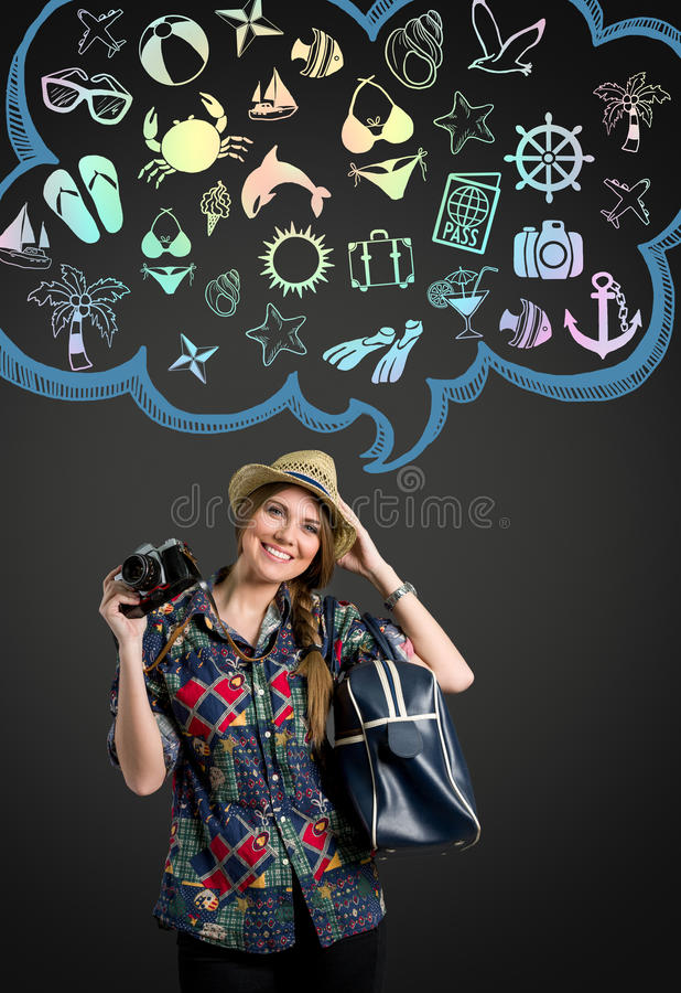 Young woman with photo camera thinking on vacation. Illustrated cloud with vacation icon royalty free stock photos