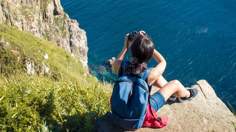 Young woman photographer sitting on the edge of cliff and taking a photo of landscape. Beautiful rocky shore stock photography