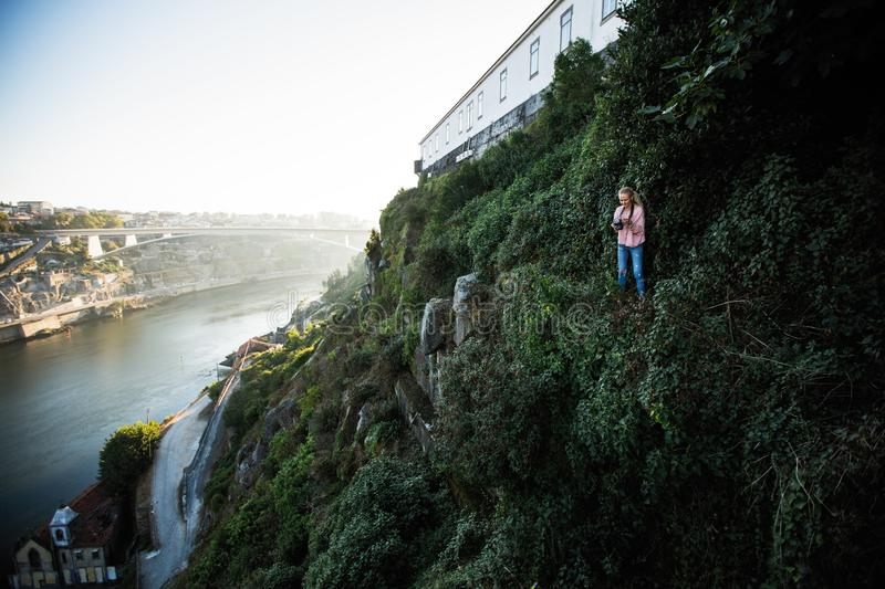 Young woman photographer standing on a green rock in front of Douro river, Porto stock photography