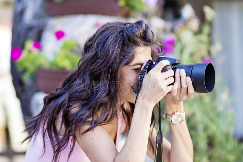 Young woman photographer taking photos outdoor stock photo