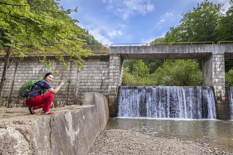 Young woman photographing a small dam with a waterfall. Sample royalty free stock image