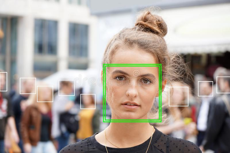 Young woman picked out by face detection or facial recognition software. Several other faces detected in crowd of people in background royalty free stock photos