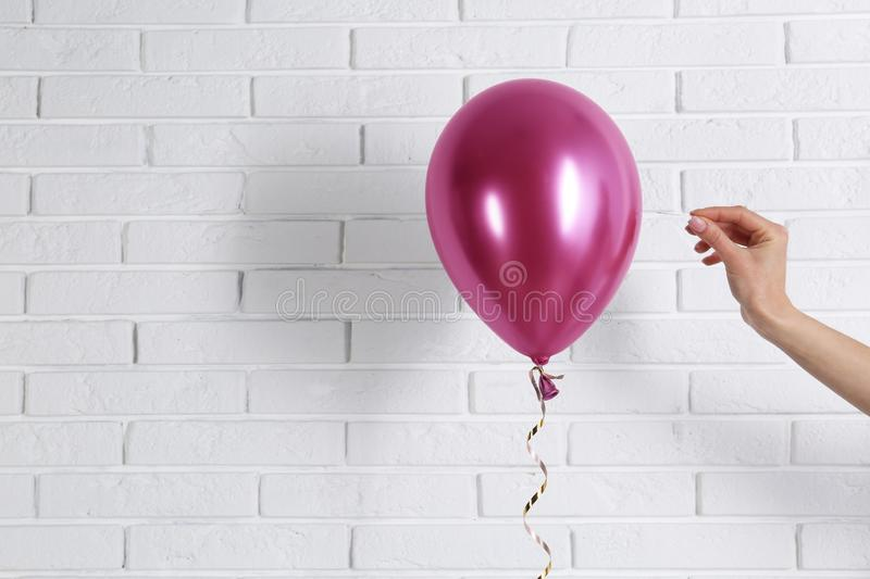 Young woman piercing bright balloon near wall, space for text royalty free stock photos