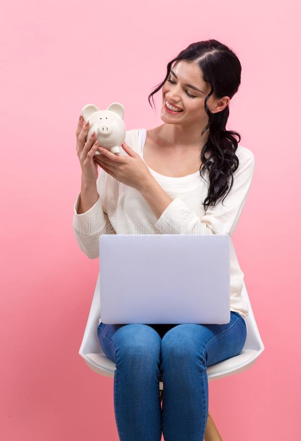 Young woman with piggy bank and laptop stock photo