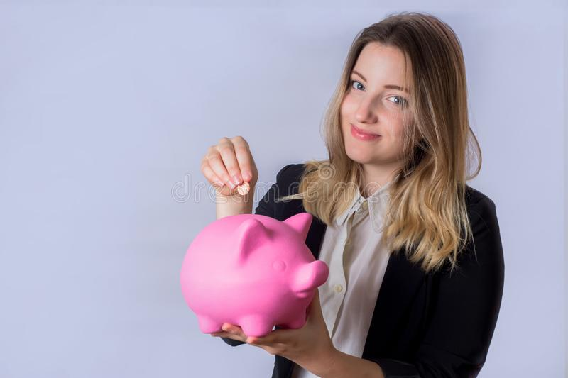 Young woman with piggy bank. Portrait of young beautiful woman putting a coin in a piggy bank on studio. Save money concept royalty free stock photo