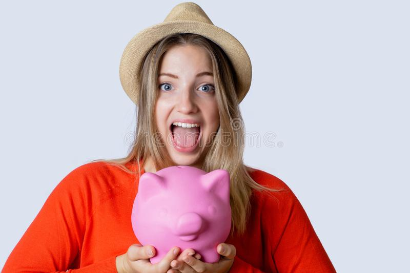 Young woman with piggy bank. Portrait of young tourist woman holding a piggy bank on studio. Save money and travel concept stock photos