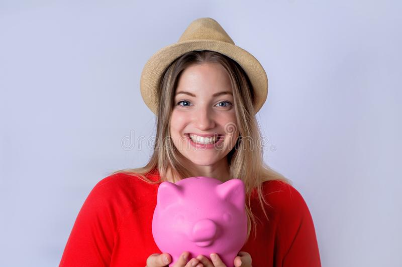 Young woman with piggy bank. Portrait of young tourist woman holding a piggy bank on studio. Save money and travel concept stock images