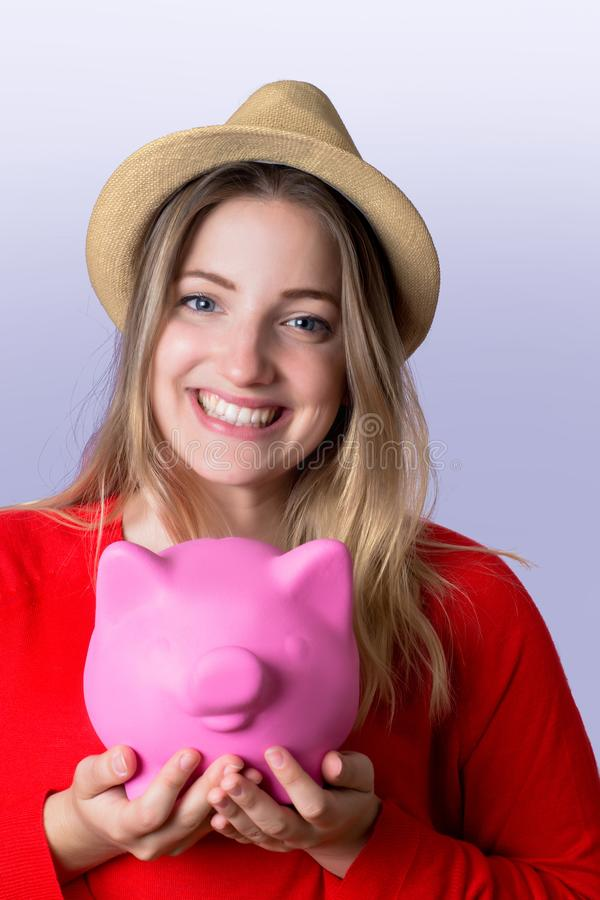 Young woman with piggy bank. Portrait of young tourist woman holding a piggy bank on studio. Save money and travel concept royalty free stock photo
