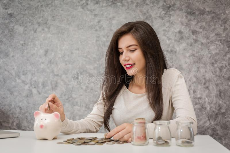 Young woman with piggy bank in the room royalty free stock photography