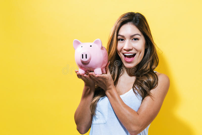 Young woman with a piggy bank. On a yellow background stock images