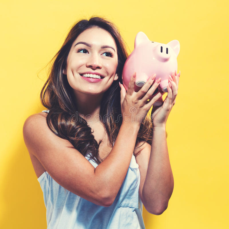 Young woman with a piggy bank. On a yellow background royalty free stock photos