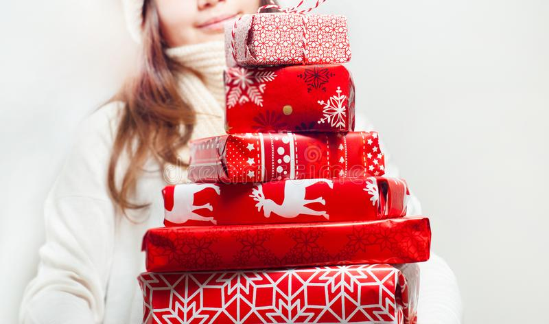 Young woman with pile of nicely packed christmas gifts stock photos