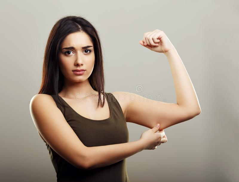 Young woman pinching arm fat skin. Young woman pinching arm fat flabby skin. Fitness and diet concept royalty free stock image