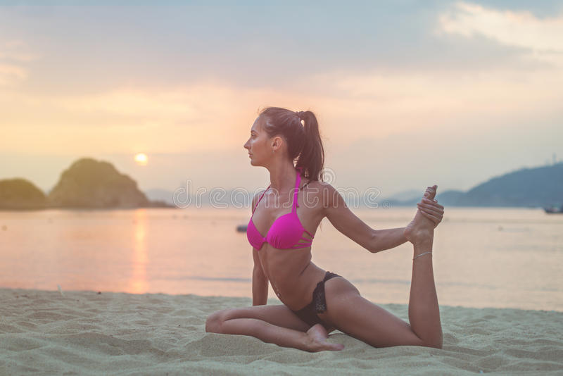 Young woman in pink bra and black panties sitting on beach stretching her legs during sunset at sea. Fitness girl doing stock images
