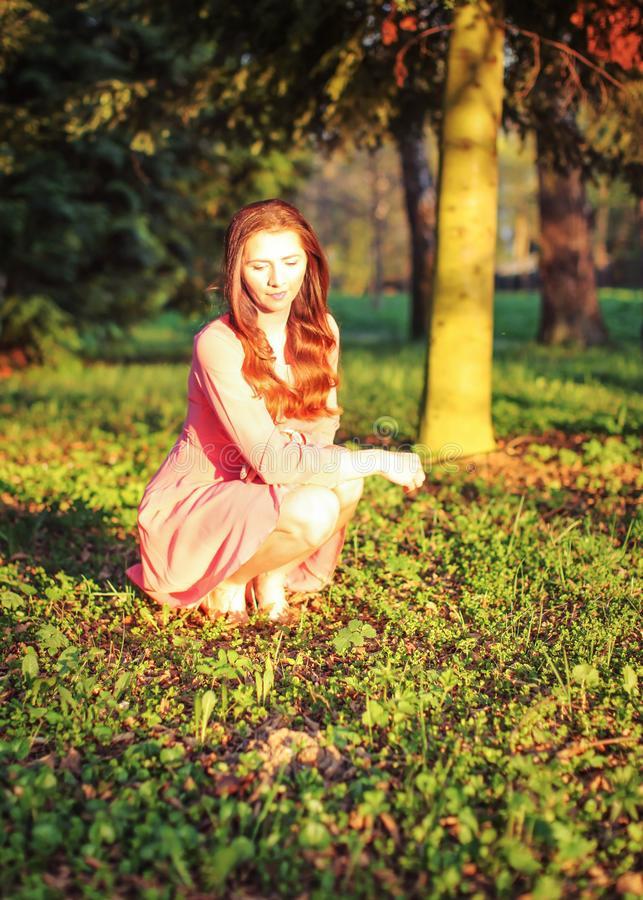 Young woman in pink dress crouching in the park, during evening. Sunset light stock photo