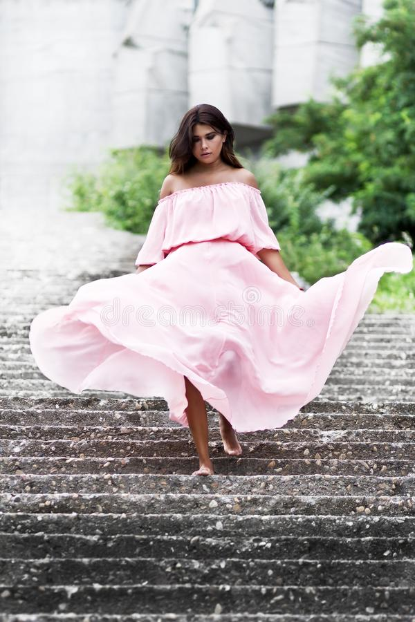 Young slim woman in pink dress. stock photography