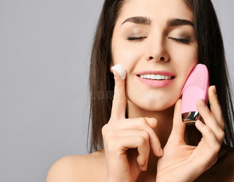 Young woman with pink face exfoliator brush silicone cleansing device for sensitive normal skin and cream and relishes softness. Young woman with pink face stock photo