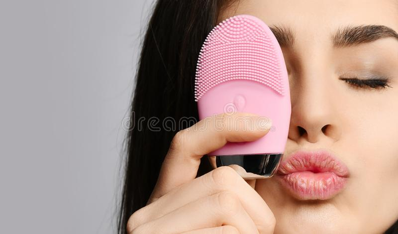 Young woman with pink face exfoliator brush silicone cleansing device for sensitive normal skin relishes incredible softness. On gray background royalty free stock photography