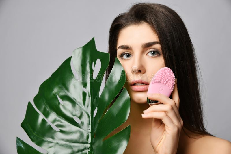 Young woman with pink face exfoliator brush silicone cleansing device for sensitive normal skin with tropical palm leaf on gray. Background stock photography