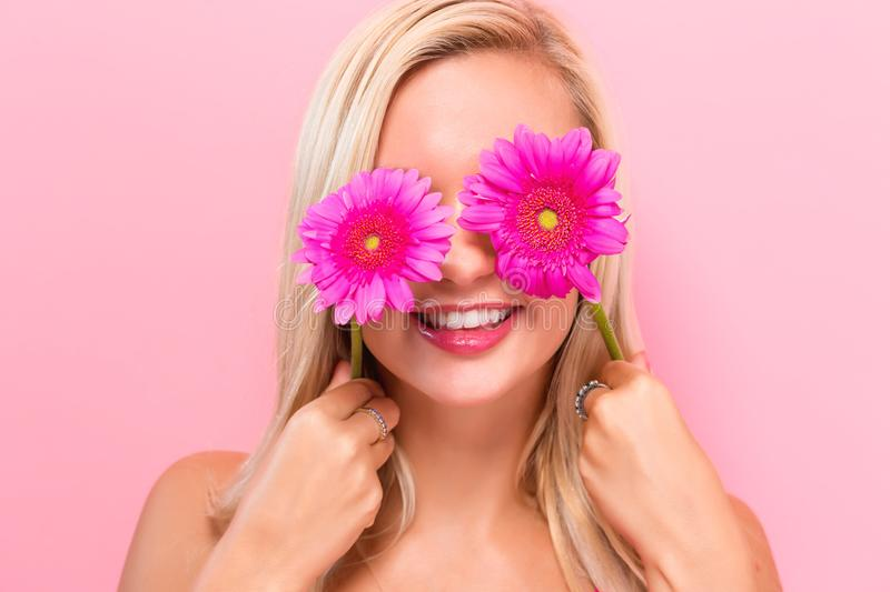 Young woman with pink garberas. On a pink background royalty free stock photography