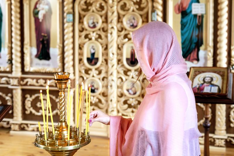 Young woman in pink headscarf praying near candles at wooden church. Female person worship God in temple royalty free stock photos