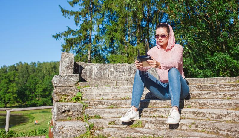 A young woman in a pink hoodie and sunglasses sitting on a stone bench and operated by remote control drone flight. stock photo