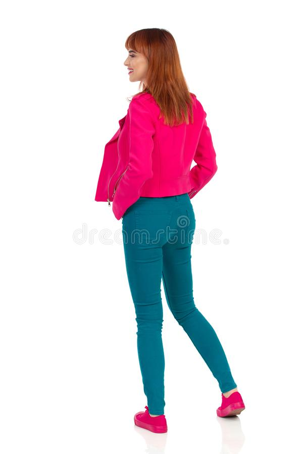 Young Woman In Pink Jacket, Teal Jeans And Sneakers Is Looking Away. Rear View. Young woman in pink jacket, green jeans and sneakers is standing and looking stock image