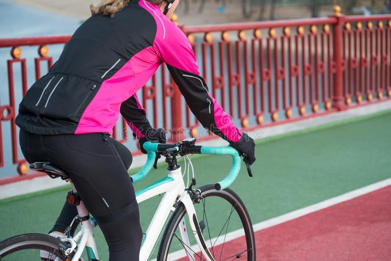 Young Woman in Pink Jacket Riding Road Bicycle on the Bridge Bike Line in the Cold Sunny Autumn Day. Healthy Lifestyle. Young Woman in Bright Pink Jacket Riding stock photography
