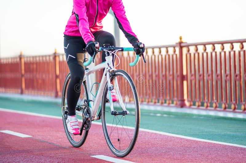 Young Woman in Pink Jacket Riding Road Bicycle on the Bridge Bike Line in the Cold Sunny Autumn Day. Healthy Lifestyle. royalty free stock photos