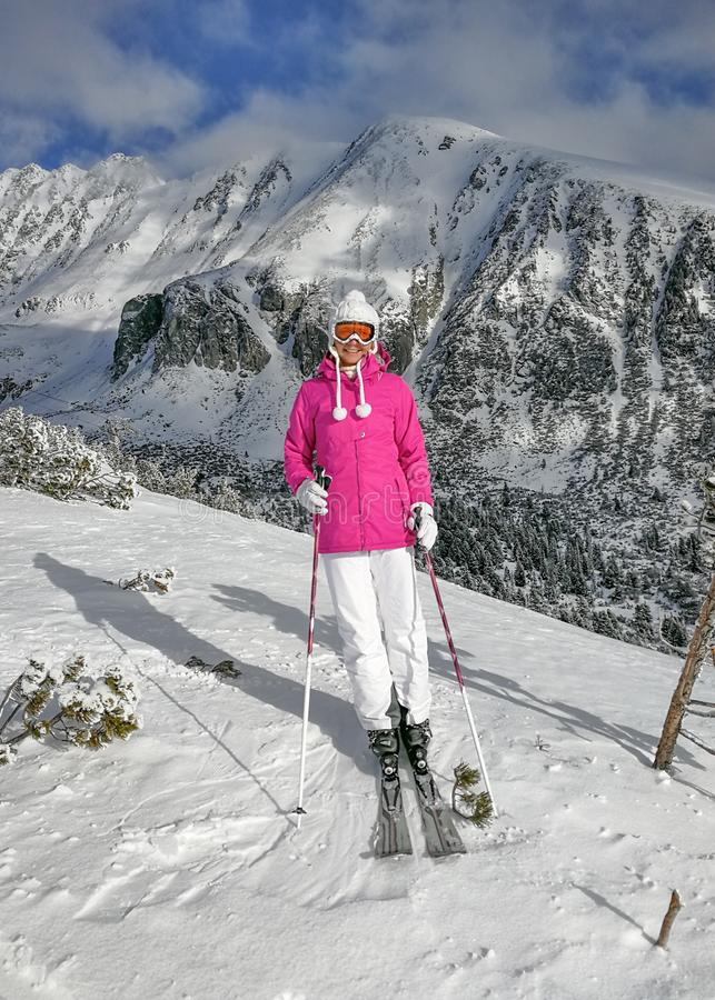 Young woman in pink jacket, ski, boots, poles, gloves and hat, posing on the piste, snow covered mountain behind her during sunny royalty free stock image