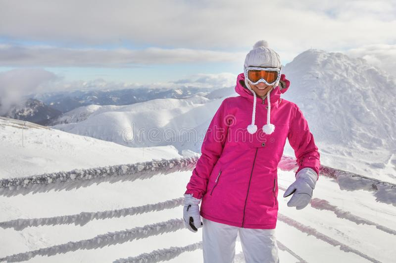 Young woman in pink jacket, wearing ski goggles, leaning on snow. Covered fence, smiling, white mountains in background royalty free stock photos