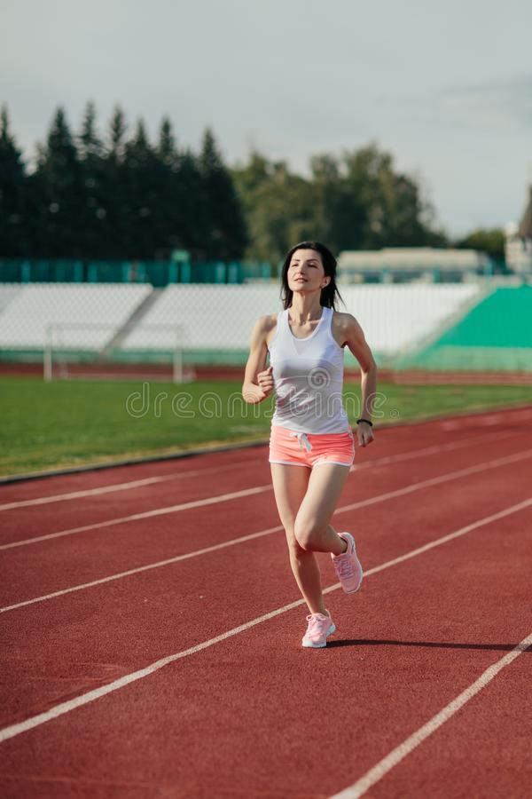 Young woman in pink shorts and tank to running during sunny morning on stadium track.  royalty free stock photo