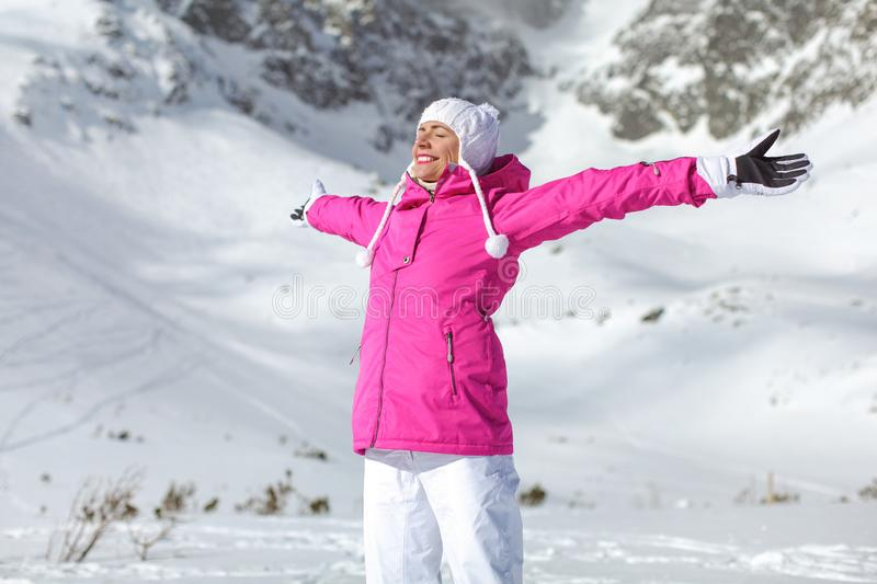 Young woman in pink ski jacket, gloves and pants, arms spread, e. Yes closed, smiling facing sun, snow covered mountain behind her stock photo
