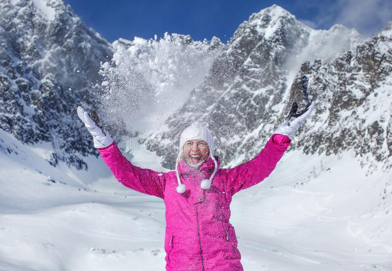 Young woman in pink ski jacket, gloves and winter hat, smiling, throwing snow in the air, sun shining on mountain behind her. Skalnate Pleso skiing resort royalty free stock images