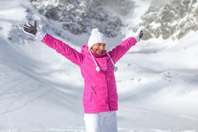 Young woman in pink ski jacket, winter hat and gloves, arms spread above, smiling, looking happy with snow covered mountain stock image