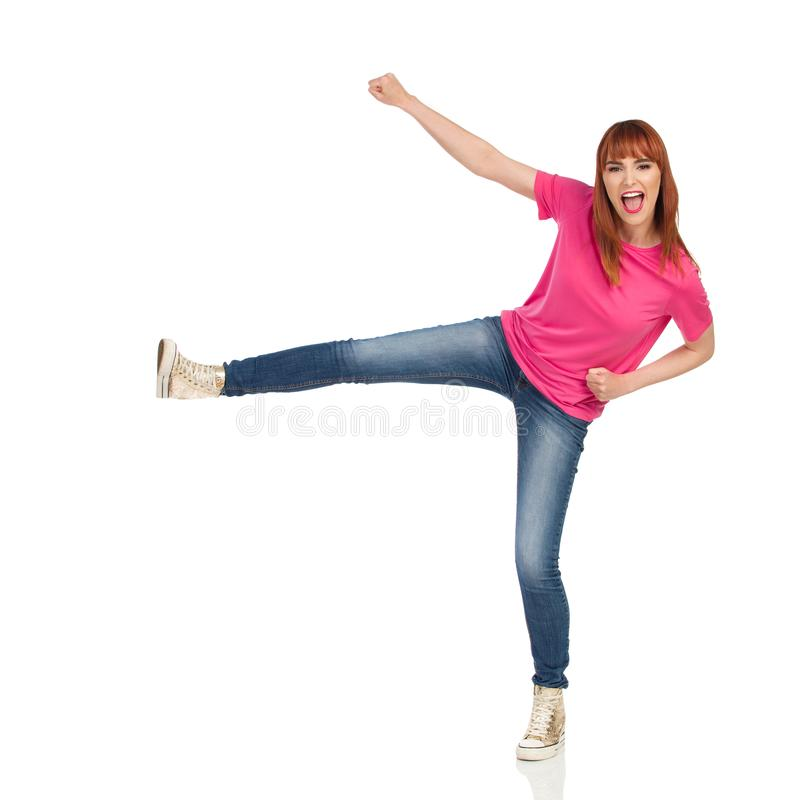 Excited young woman in pink t-shirt, jeans and gold sneakers is kicking and shouting. Full length studio shot isolated on white. Young woman in pink t-shirt stock photos