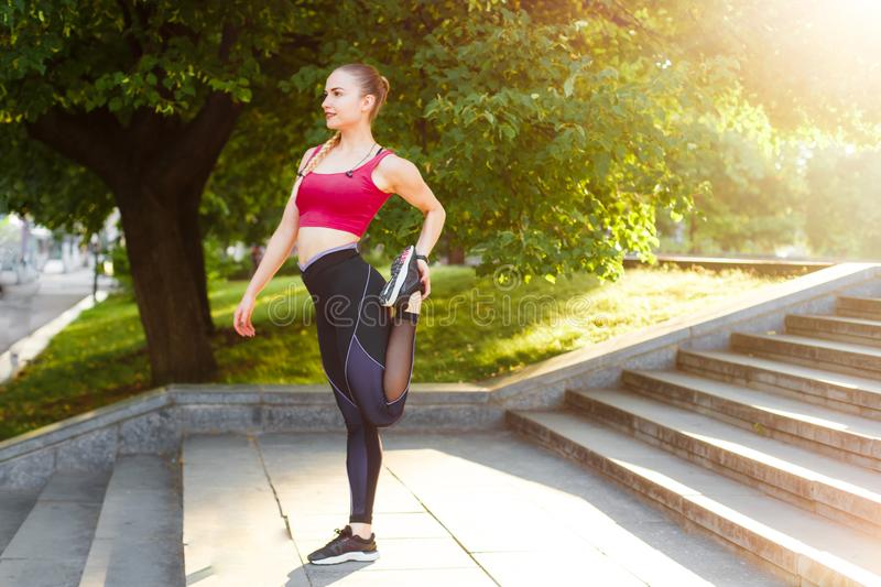 A young woman stretches out after a morning run in the city. royalty free stock image