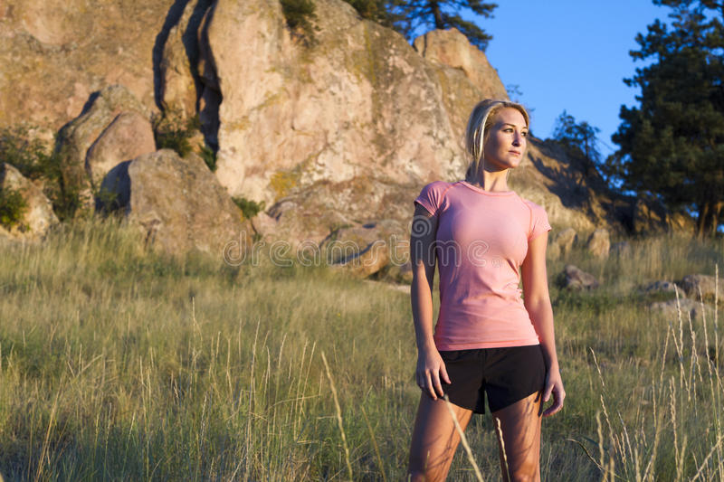Young woman in pink top taking a break from an early morning run. stock images