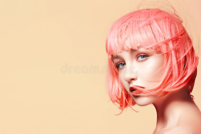 Young woman in pink wig. Beautiful model with fashion makeup. Bright spring look. hair color, medium hairstyle royalty free stock photo