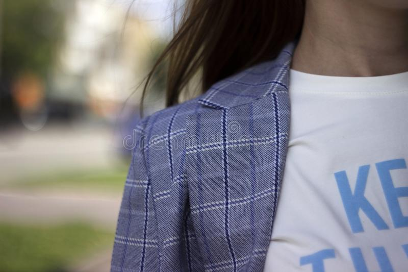 Young woman in plaid jacket, white t-shirt and jeans, street style, fashion.  stock photo