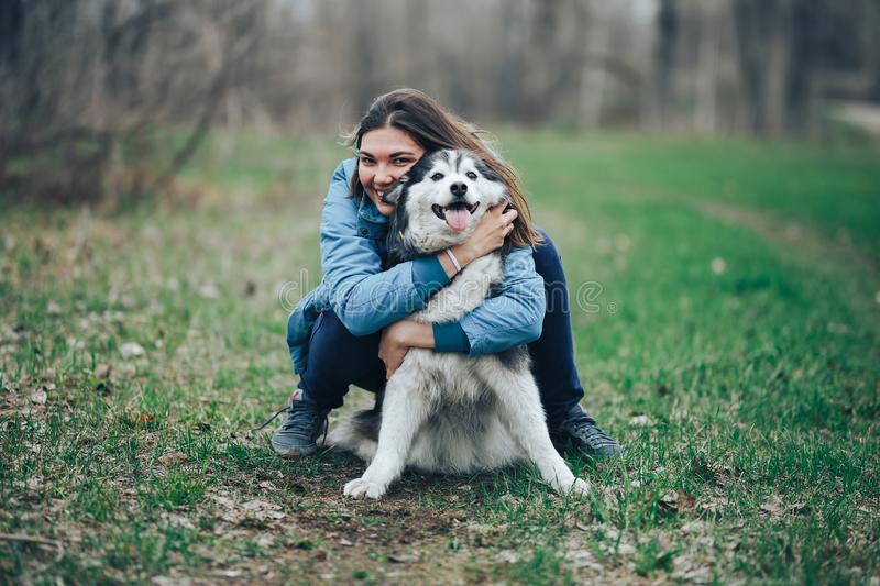 Young woman play with husky dog for a walk in spring forest. laughing having fun, happy with pet royalty free stock photography