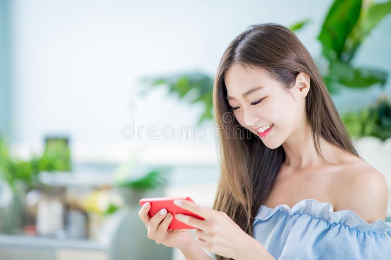 Young woman play mobile game. And use smart phone at home royalty free stock photography