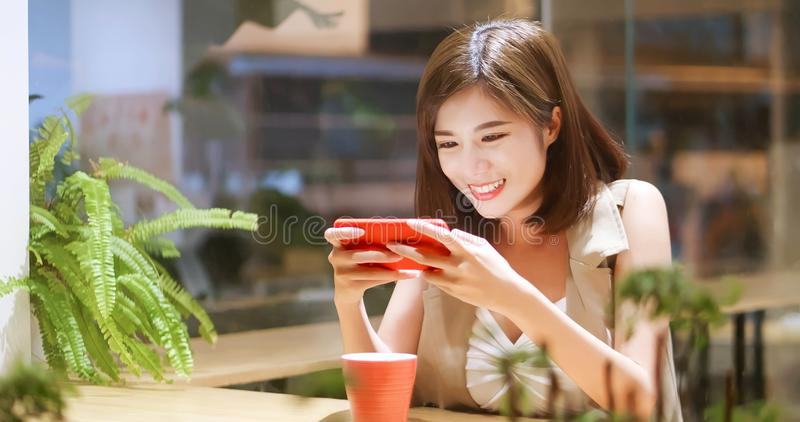 Young woman play mobile game. Happily in coffee shop royalty free stock image