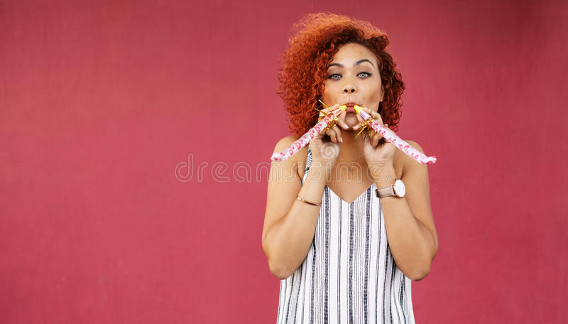 Young woman in playful mood blowing party whistles. royalty free stock photo