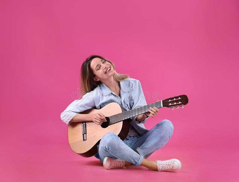 Young woman playing acoustic guitar royalty free stock photography
