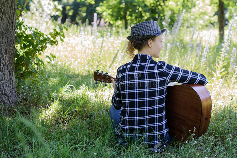 Young woman playing an acoustic guitar in a meadow stock photos
