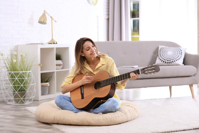 Young woman playing acoustic guitar in room. Young woman playing acoustic guitar in living room royalty free stock images